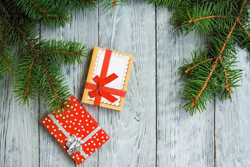 Deux boîtes de Noël de fête sur un fond en bois de vintage gris avec les branches d'arbre vertes photo libre de droits