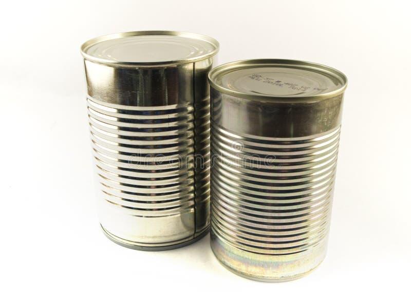 Deux boîtes en fer blanc de nourriture brillante sur le fond blanc image libre de droits