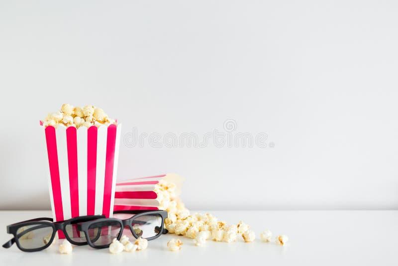 deux boîtes rayées avec le maïs éclaté, les verres 3d et l'espace de copie au-dessus du blanc images libres de droits