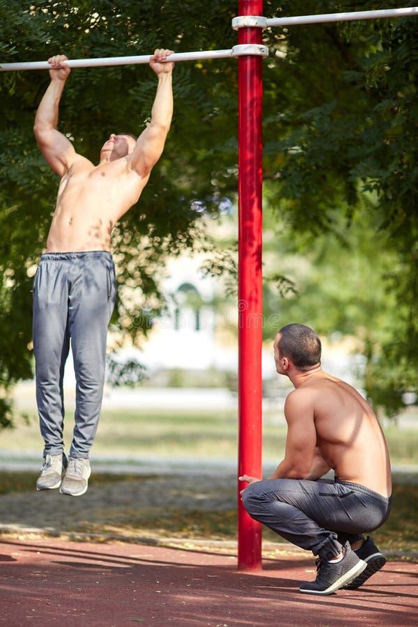 Deux bodybuilders d'amis sur les barres horizontales sur un fond brouillé Concept d'athlétisme images libres de droits