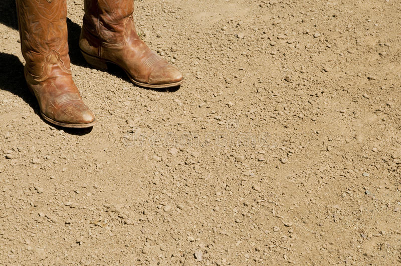 Deux bottes de cowboy occidentales sales se tenant sur l'au sol de saleté images libres de droits