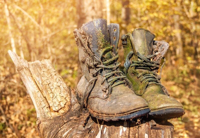 Deux bottes militaires usées et anciennes se dressent contre une forêt par beau temps Une paire de chaussures de travail abandonn image stock