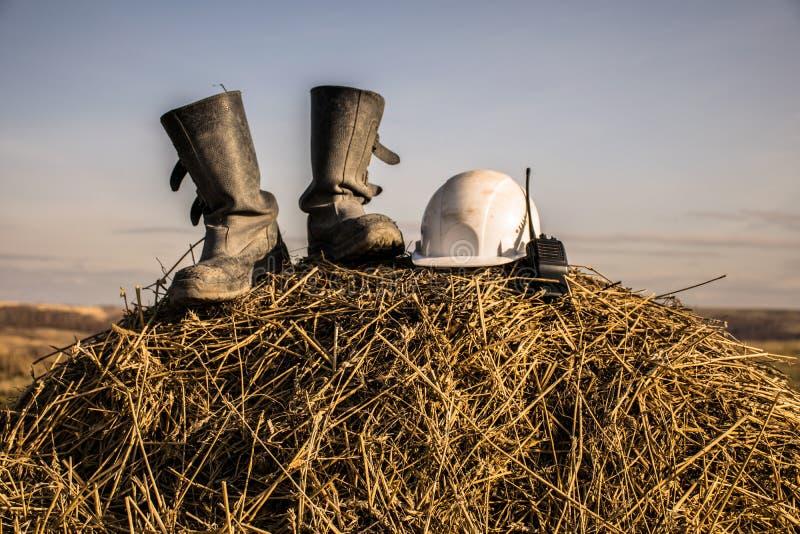 Deux bottes noires sur une meule de foin sur des bottes ensoleillées d'un noir de daytwo, un casque et un talkie - walkie sur un photo libre de droits