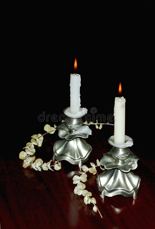Deux bougies allumées dans des chandeliers d'elegantnyh photographie stock libre de droits