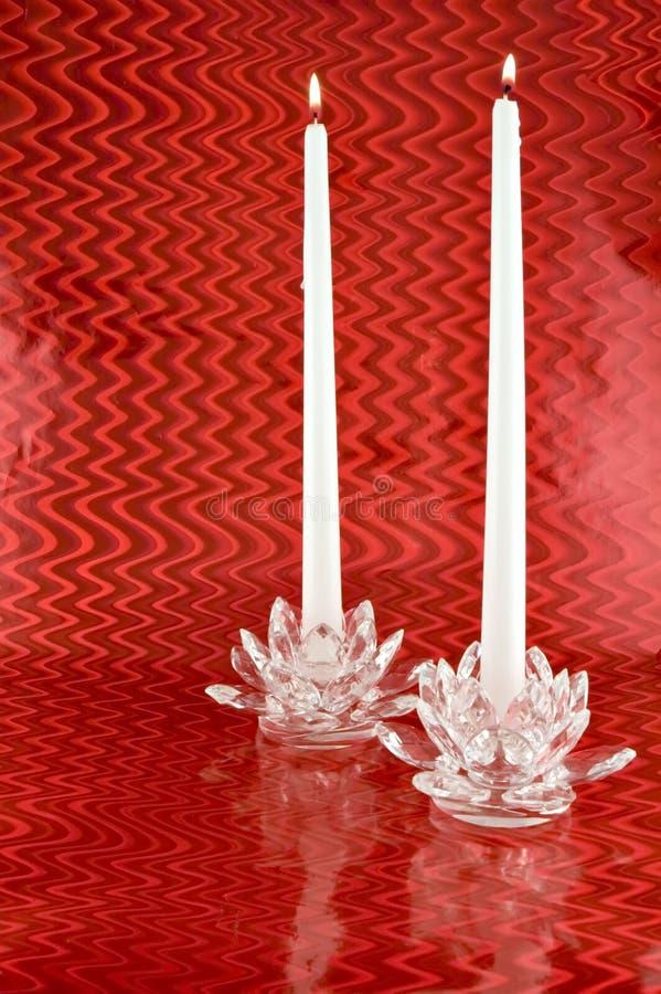Deux bougies blanches dans les bougeoirs en cristal avec Backgrounc rouge photo libre de droits
