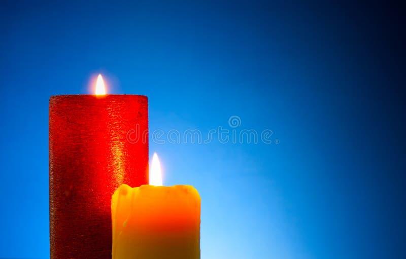Deux bougies colorées brûlantes images stock