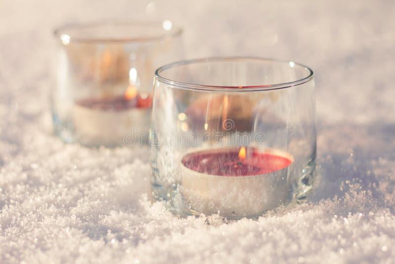 Deux bougies dans les verres sur la neige image libre de droits