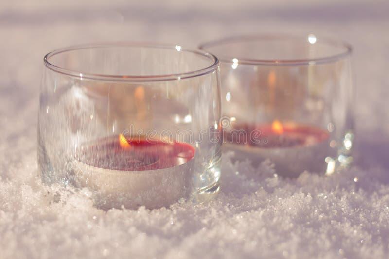 Deux bougies dans les verres sur la neige images stock