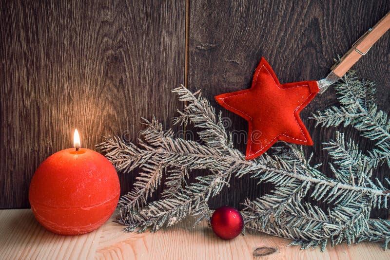 Deux bougies rouges avec le décor de Noël sur le fond en bois photographie stock