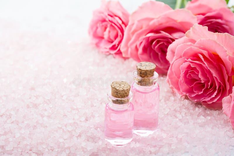 Deux bouteilles avec de l'huile rose, des cristaux de sel de station thermale et des roses roses photo stock