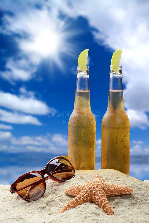Deux bouteilles de bière froide avec la chaux dans un bel arrangement tropical de plage photographie stock libre de droits