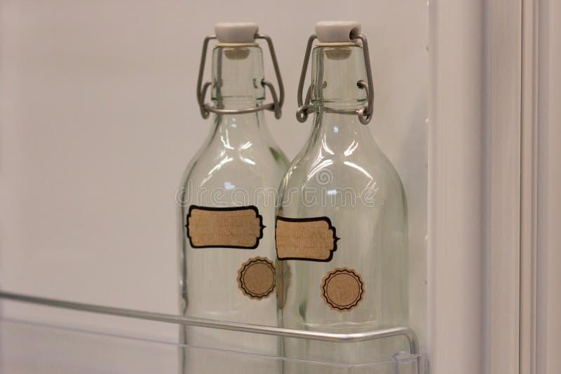 Deux bouteilles en verre vides se tiennent dans la porte de réfrigérateur photo libre de droits