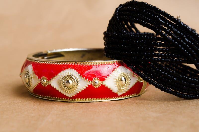 Deux bracelets Bracelet perlé et bracelet en métal Bijutrei femelle Une paire de bijoux Bracelet rouge Ressort Fleur de ressort photos libres de droits