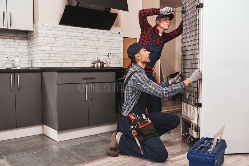 Deux bricoleurs avec le réfrigérateur Mécanique de jeunes hommes vérifiant le réfrigérateur images stock