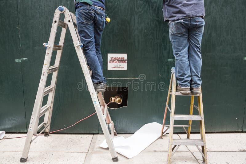 Deux bricoleurs sur des échelles photo stock