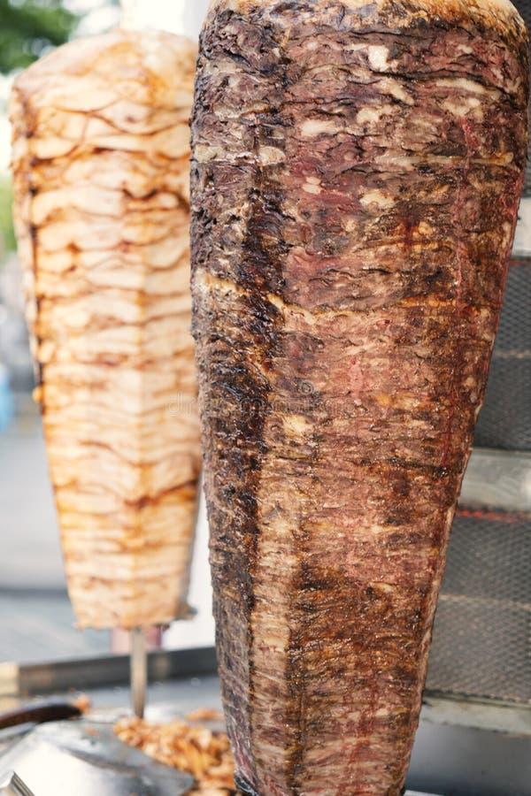 Deux brochettes de viande tournantes de poulet et d'agneau grillées dans le gril d'acier inoxydable et prêtes à servir photographie stock libre de droits