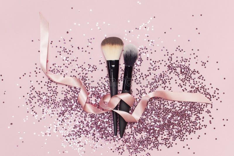 Deux brosses cosmétiques différentes de maquillage avec le ruban rose et confettis olographes de scintillement sous forme d'étoil photographie stock