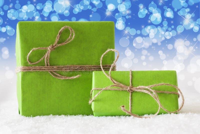 Deux cadeaux verts sur la neige, effet bleu de Bokeh images libres de droits