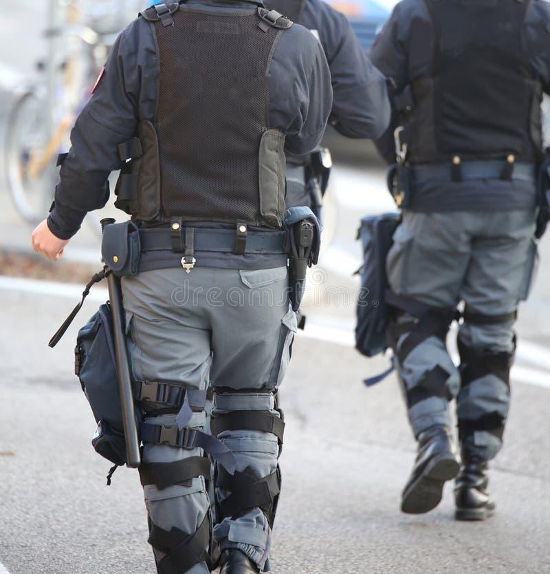 deux cannettes de fil de police d'anti-émeute patrouillent les rues du photos stock