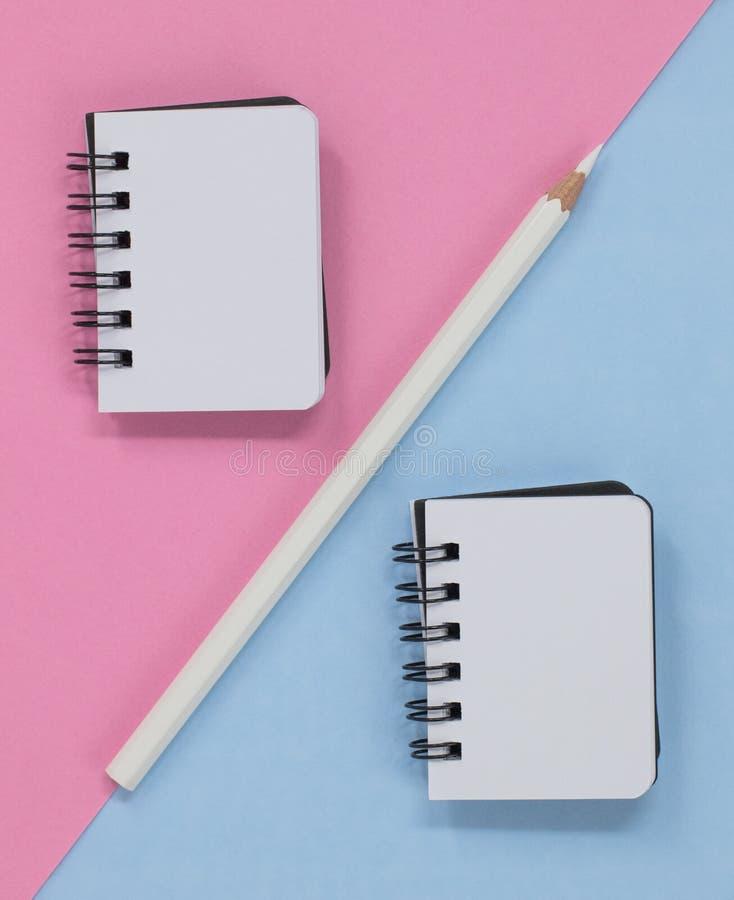 Deux carnets de notes ? spirale ouverts crayonnent sur un rose et un fond diagonal bleu Configuration plate avec l'espace de copi photographie stock