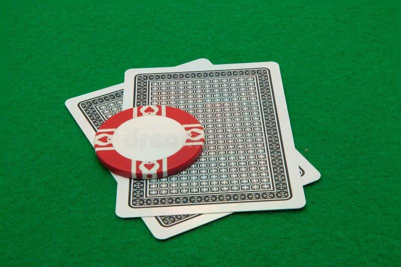 Deux cartes faisant face vers le bas avec la puce de casino sur le vert images stock