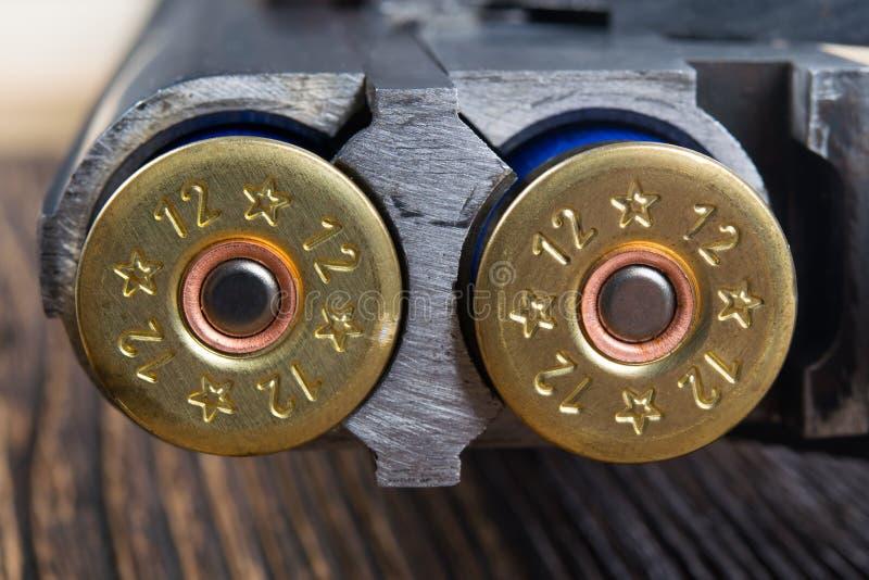 deux cartouches d'or dans des armes à deux coups, sur un fond en bois photos stock