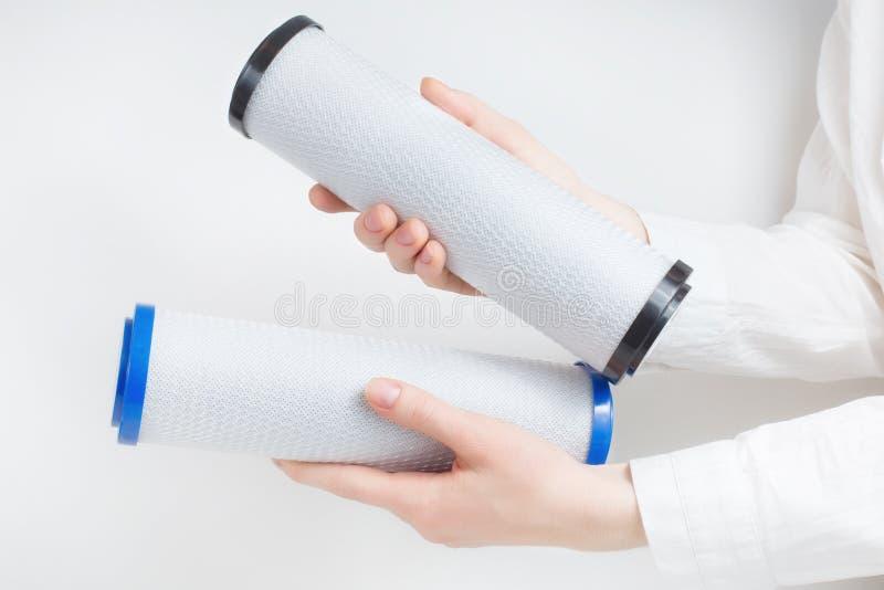Deux cartouches filtrantes de l'eau dans des mains humaines image stock