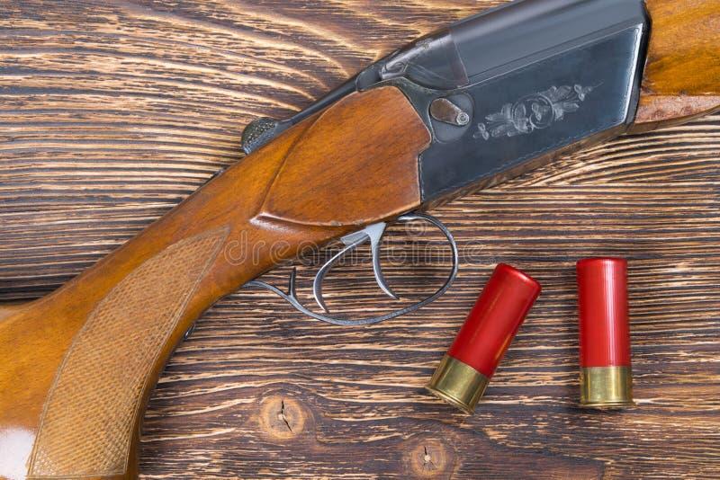 Deux cartouches rouges sur un conseil en bois foncé, et un fusil de chasse photographie stock libre de droits