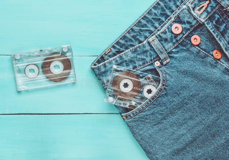 Deux cassettes sonores dans des jeans empochent sur une surface en bois bleue Technologie de media des années 80 photos stock