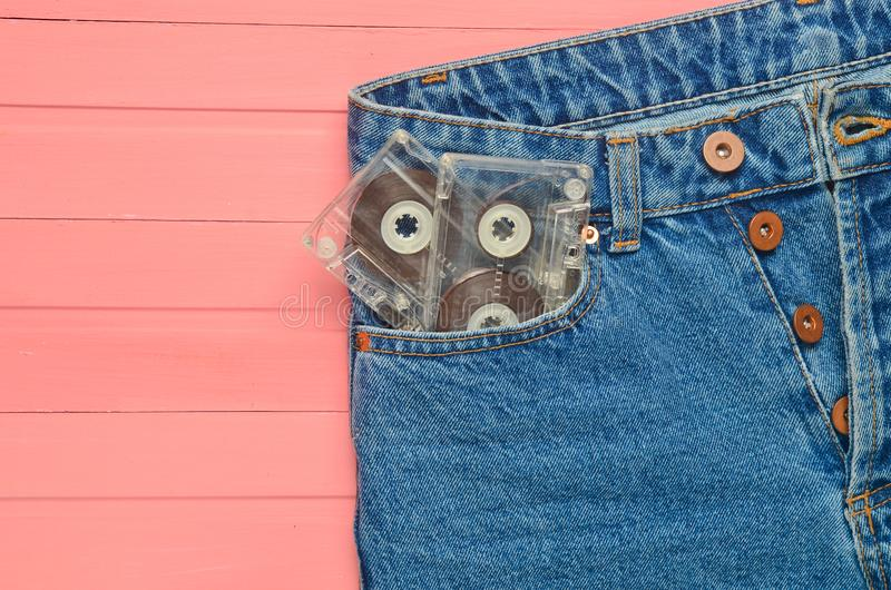 Deux cassettes sonores dans des jeans empochent sur une surface en bois rose Technologie de media des années 80 photo stock