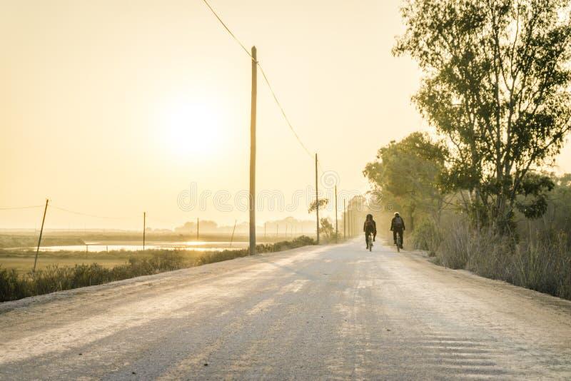 Deux cavaliers de bicyclette sur une route de la poussière dans Algarve, Portugal image stock