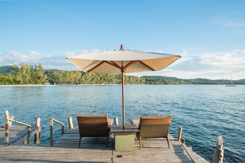 Deux chaises échouent et parapluie sur le bureau en bois contre le ciel bleu photo stock