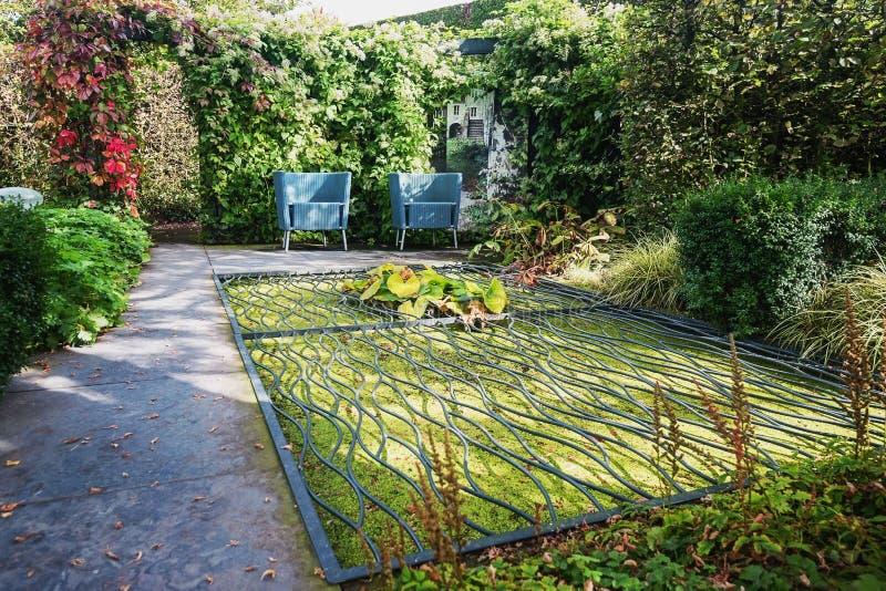 Deux chaises de jardin bleues de conception pour l'étang du lequel est couvert photo libre de droits
