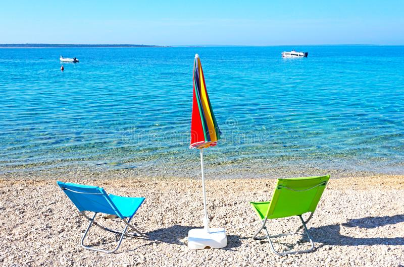 Deux chaises et parapluies de soleil sur le Pebble Beach devant la mer bleue image stock