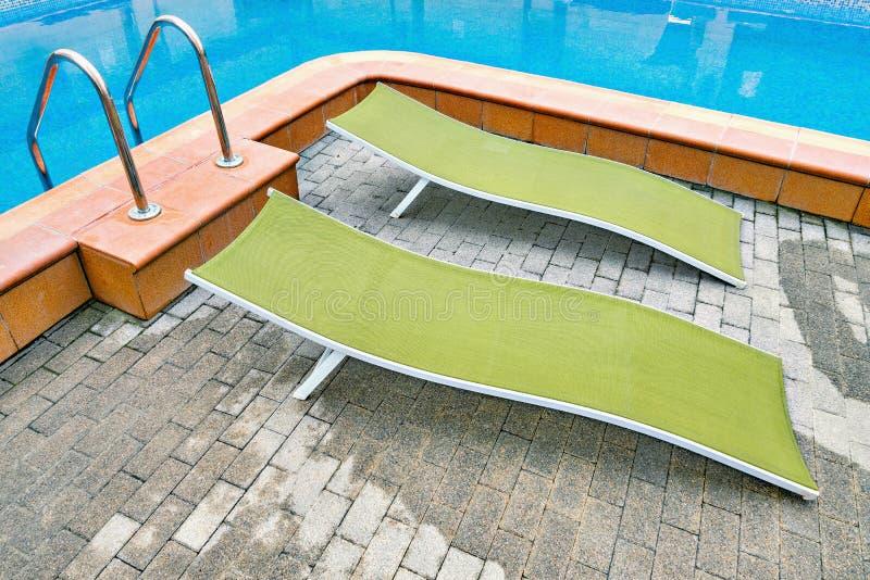 Deux chaises longues par la piscine photographie stock libre de droits