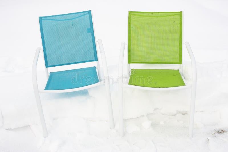 Deux chaises multicolores se tiennent dans une congère, contre un s blanc photo libre de droits