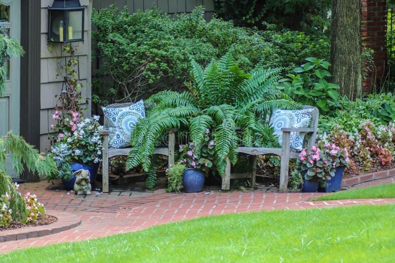 Deux chaises rustiques avec les oreillers décoratifs en dehors de la maison avec la fougère géante et les usines mises en pot  images libres de droits