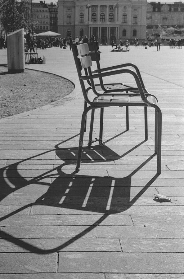 Deux chaises vides appréciant les derniers jours chauds de l'automne dans la place de l'opéra à Zurich image libre de droits