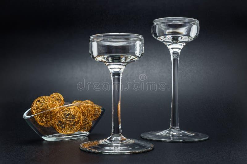 Deux chandeliers en verre se tenant sur un noir, fond brillant, à côté d'un petit vase avec les boules d'or en métal image stock