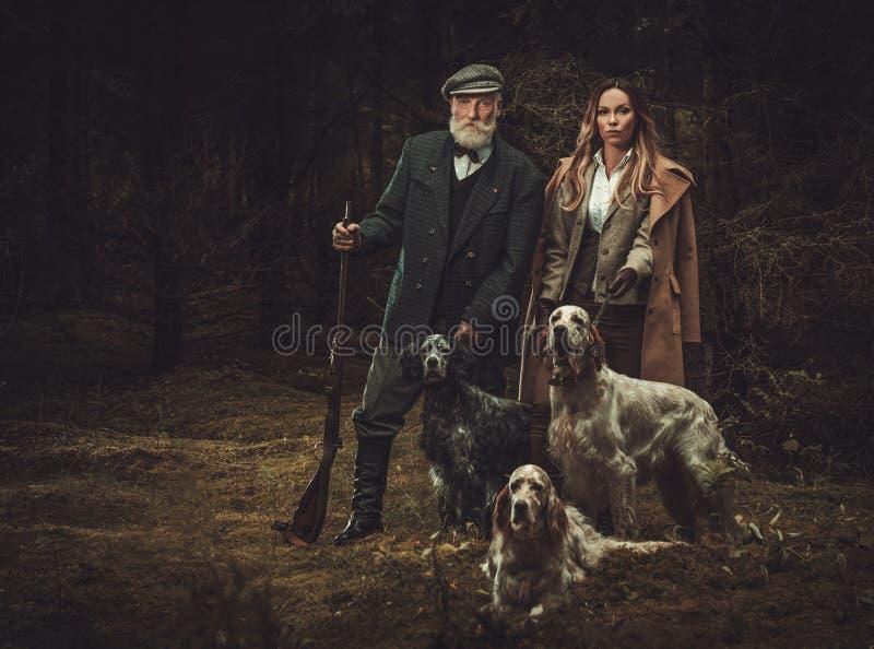 Deux chasseurs avec des chiens et des fusils de chasse dans un habillement traditionnel de tir, posant sur un fond foncé de forêt photos libres de droits
