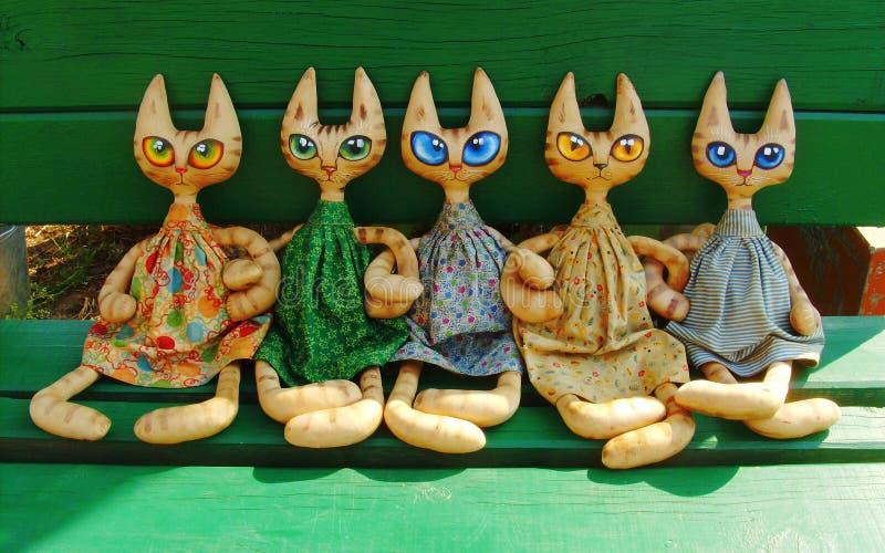 Deux chats de jouet de textile avec de grands yeux expressifs se reposent sur un banc vert un jour ensoleill? d'?t? et tiennent l image libre de droits
