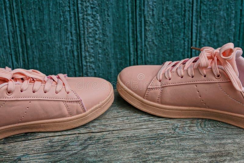 Deux chaussures sportives roses se tiennent sur un conseil gris contre un mur vert image libre de droits