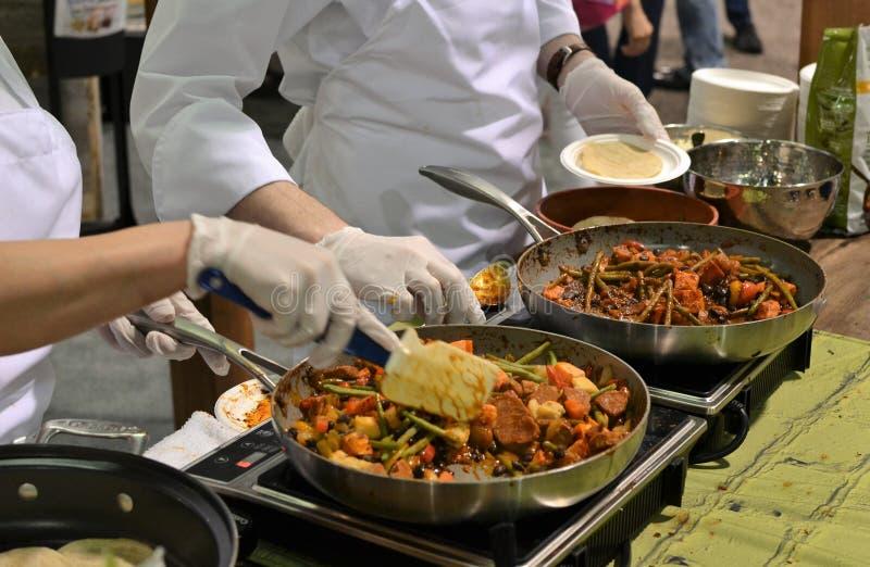 Deux chefs à un salon commercial de produits naturels prélèvent la nourriture et conduisent une démo de nourriture image libre de droits