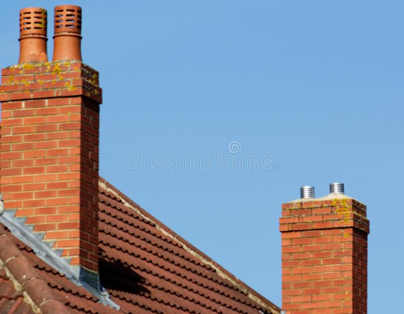 Deux cheminées sur une maison avec le ciel bleu photos stock