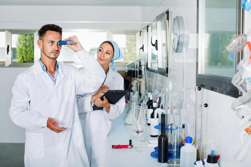 Deux chercheurs dans le manteau blanc vérifiant l'acidité de vin dans le laboratoire photos libres de droits