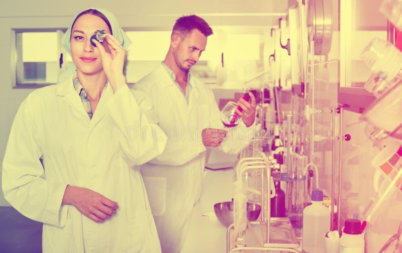 Deux chercheurs dans le manteau blanc vérifiant l'acidité de vin dans le laborator images libres de droits