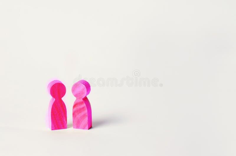 Deux chiffres en bois roses des personnes se tiennent sur le fond blanc deux personnes d'orientation homosexuelle le concept du r photo stock