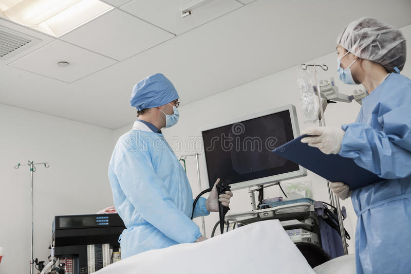 Deux chirurgiens se préparant à la chirurgie, patient se couchant images stock