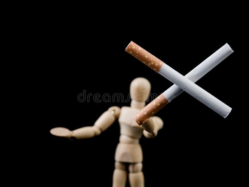 Deux cigarettes en forme croisée se tenant par l'homme en bois figurent, ` que vous mettez le besoin du ` t de fumer pour être co photographie stock