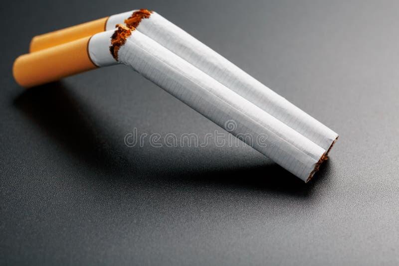 Deux cigarettes sous forme de fusil de chasse ? deux coups sur un fond noir avec l'espace de copie Cessez le fumage Le concept de images libres de droits